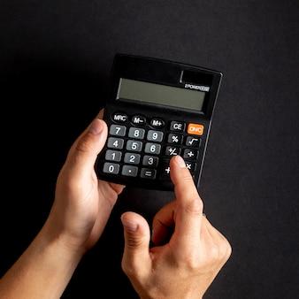 Mãos usando mini calculadora preta