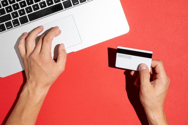 Mãos usando o computador e segurando um cartão de crédito