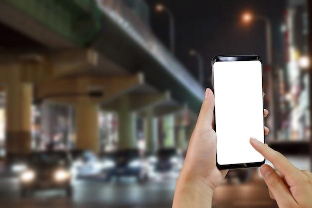 Mãos usando o telefone móvel do modelo na estrada com transporte na cidade no nighttime.
