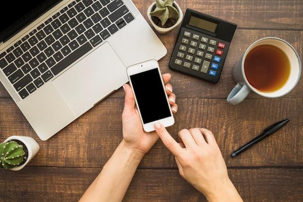 Mãos, usando, smartphone, em, área de trabalho