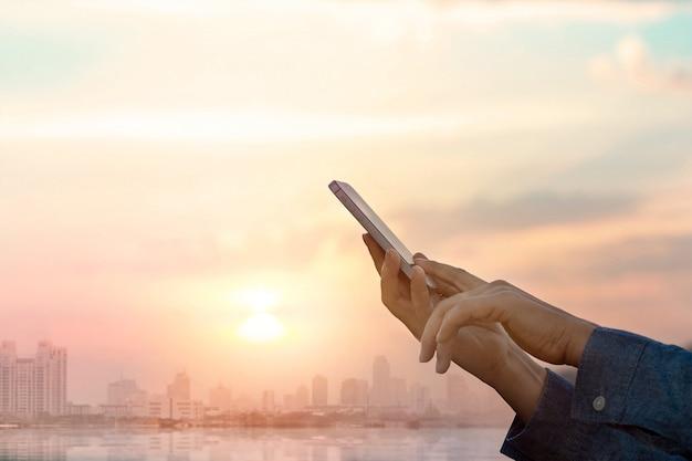 Mãos usando smartphone na cidade no fundo por do sol
