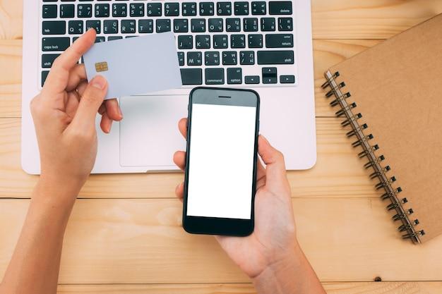 Mãos usando telefone inteligente e cartão de crédito para o conceito de compras on-line