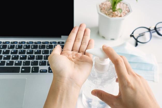 Mãos usando um desinfetante na frente do computador
