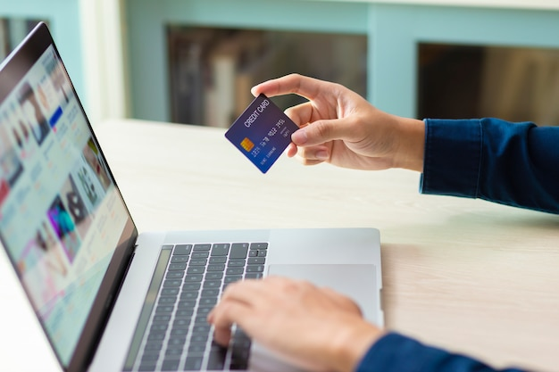 Mãos usando um laptop e cartão de crédito para pagamento on-line