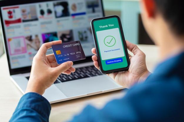 Mãos usando um telefone e cartão de crédito para pagamento on-line