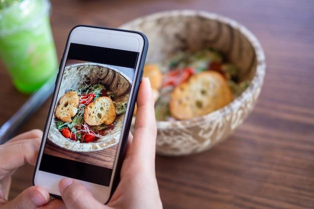Mãos usando um telefone para tirar fotos de comida