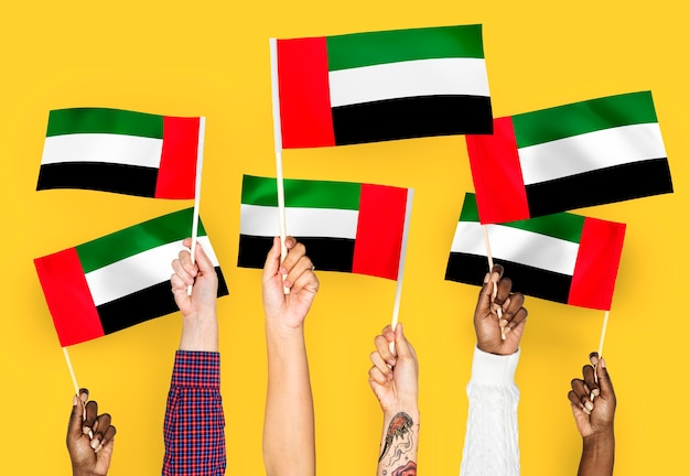 Mãos, waving, bandeiras, de, a, emirates árabes unidos