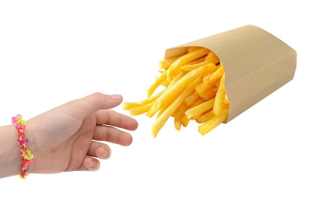 Mãozinha tirando batatas fritas da caixa de papel kraft, isolada no fundo branco.
