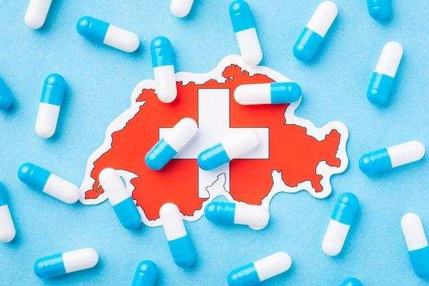 Mapa da suíça com muitos comprimidos ao redor. símbolo de péssimo estado de saúde no país, disseminação de muitas enfermidades e enfermidades