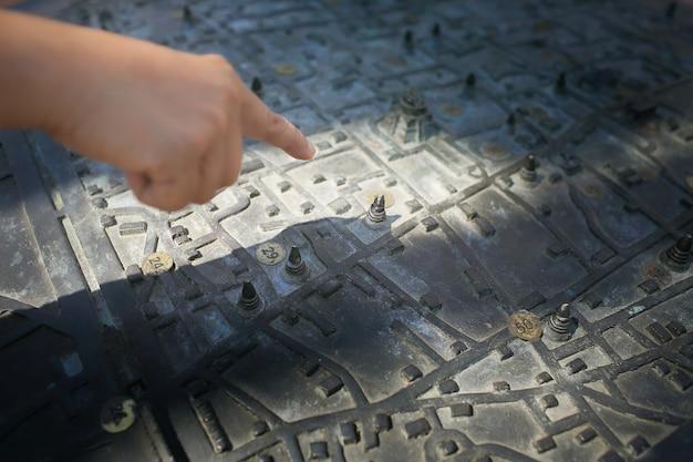 Mapa de metal antigo com a mão da menina