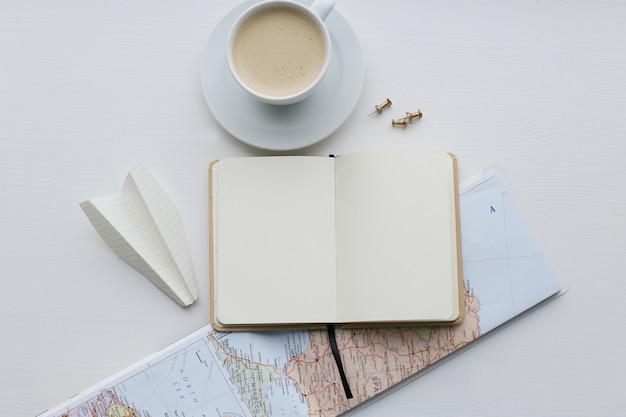 Mapa de viagem, diário e xícara de café