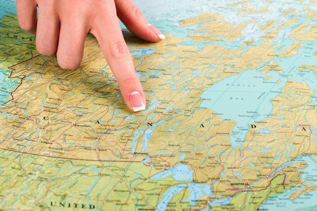 Mapa do canadá no atlas. dedo feminino aponta para o canadá. basta voar pelo oceano. o maior vizinho da américa.