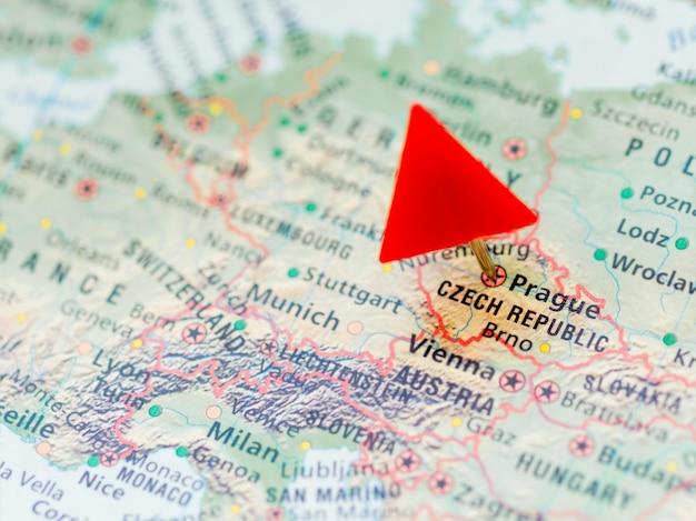 Mapa do mundo com foco na república checa com capital praga. o triângulo vermelho aponta para ele.