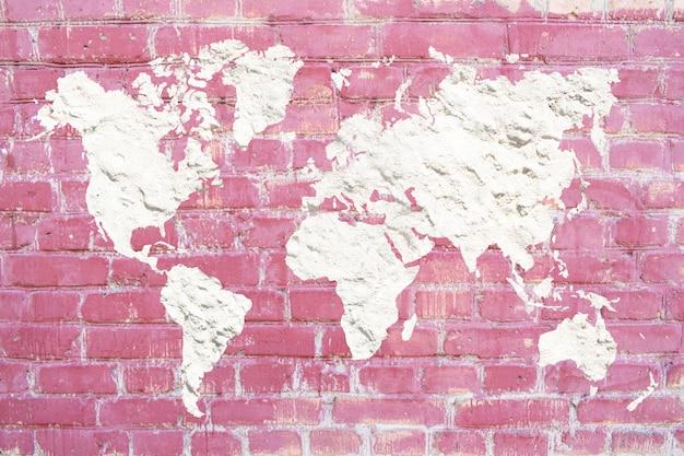 Mapa do mundo do emplastro do cimento branco em um fundo cor-de-rosa do tijolo. parede de grunge de tijolo rosa