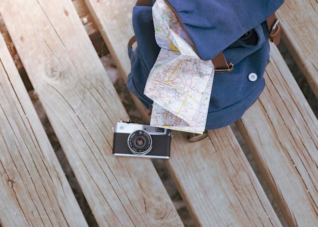 Mapa e câmera fotográfica na mochila na natureza, um conceito de traveller.travel.