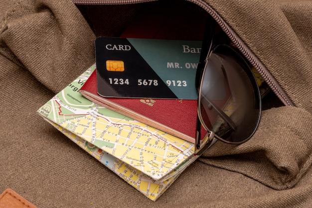 Mapa turístico, cartão de crédito, óculos de sol, passaporte no bolso