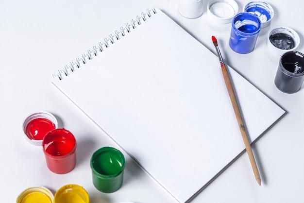Maquete artística em um fundo branco. ferramentas de desenho de tinta acrílica, pincel, bloco de notas. copie o espaço