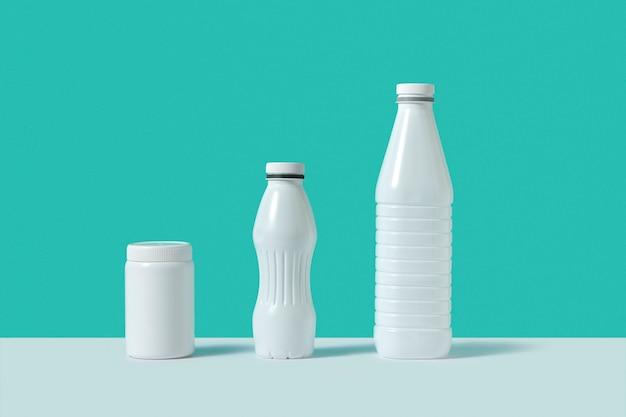 Maquete branco em branco de garrafas de plástico de diferentes tamanhos e formas em uma parede duotônica com sombras e espaço de cópia.