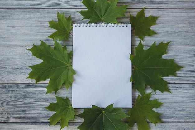Maquete, caderno em um fundo de madeira, folhas de plátano