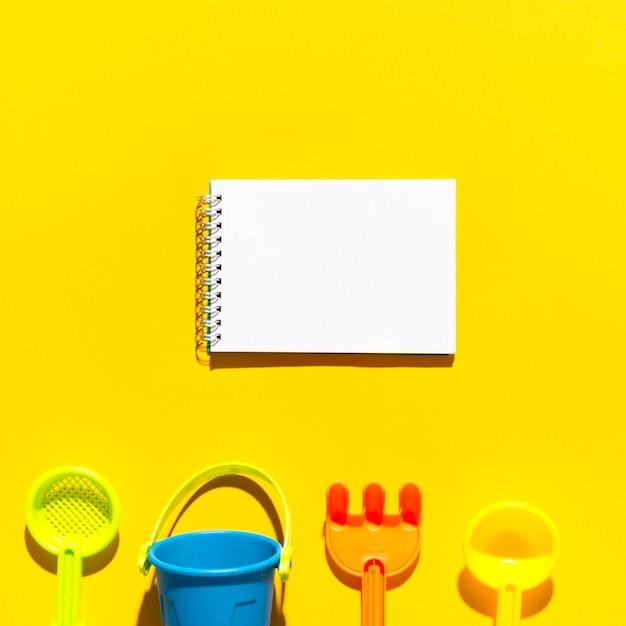 Maquete com bloco de anotações em branco para texto e brinquedos