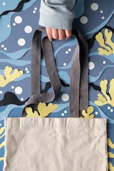 Maquete com cópia-espaço. mão segura a bolsa de lona no fundo subaquático do mar abstrato de papel cortado