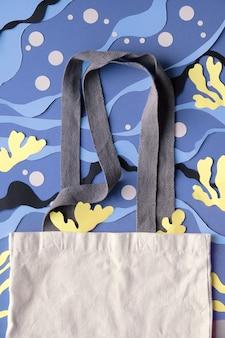 Maquete com cópia-espaço para seu projeto. saco de lona em branco sobre fundo subaquático de papel cortado