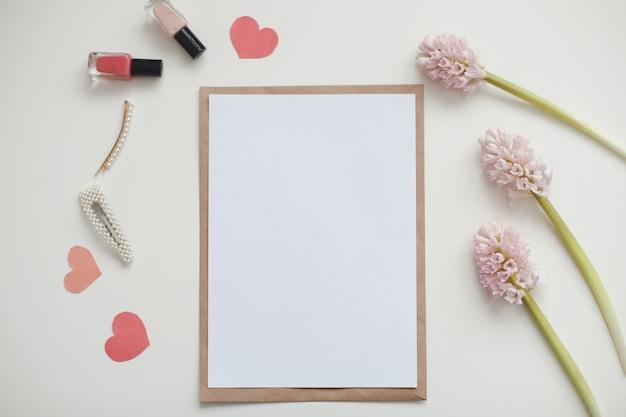 Maquete com flores cor de rosa e papel em branco com espaço de cópia.