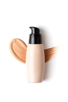 Maquete com maquiagem rosto fundação garrafa e gota borrada de corretivo sobre o fundo branco