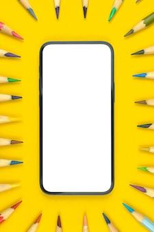 Maquete da área de trabalho plana da escola com smartphone moderno, espaço de cópia e tela branca em branco, área de trabalho amarela com lápis de cor, foto da vista superior