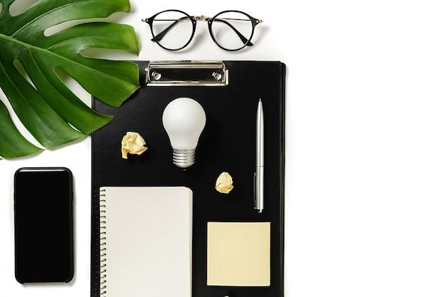 Maquete da área de transferência, folhas de monstera, caneta, caderno, smartphone moderno, óculos e lâmpada