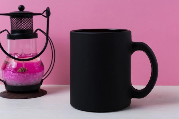 Maquete da caneca de café com lanterna de vela de metal preto