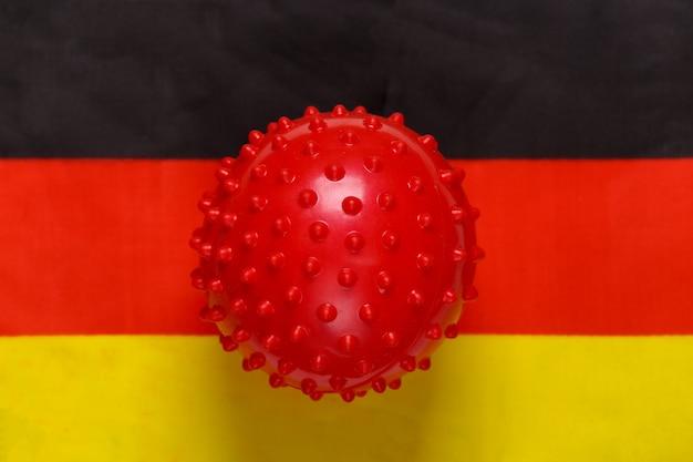Maquete da cepa de vírus covid-19 no fundo da bandeira da alemanha