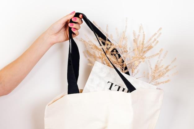 Maquete da mão de uma mulher segurando ecobag reutilizável de algodão branco com alças pretas com flores secas e n ...