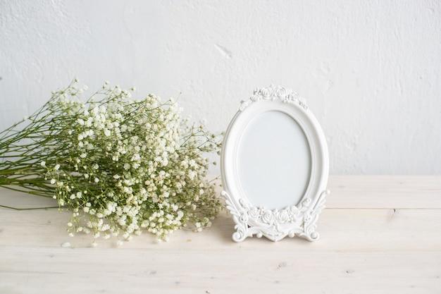 Maquete da moldura branca do retrato na mesa de madeira vaso de cerâmica moderno com gypsophila fundo branco da parede interior escandinavo