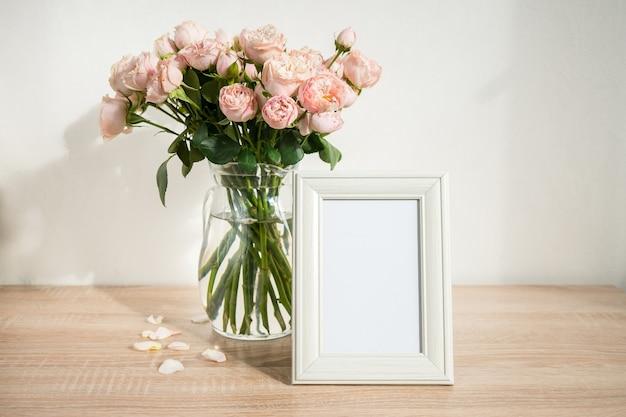 Maquete da moldura branca do retrato na mesa de madeira vaso de vidro moderno com rosas fundo da parede branca interior escandinavo