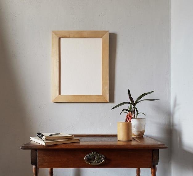 Maquete da moldura de madeira. vaso de flores em uma pilha de livros sobre uma velha mesa de madeira. composição em uma superfície de parede branca