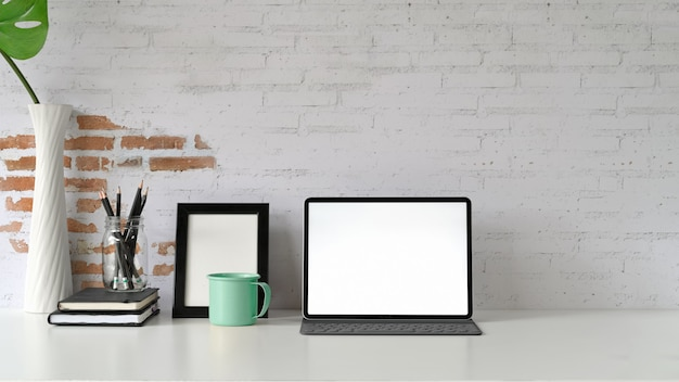 Maquete da tela em branco tablet na mesa de madeira branca e suprimentos