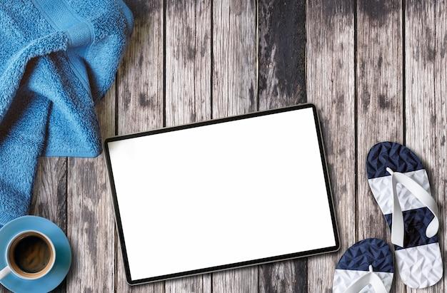 Maquete da tela em branco tablet, toalha, xícara de café na mesa de madeira