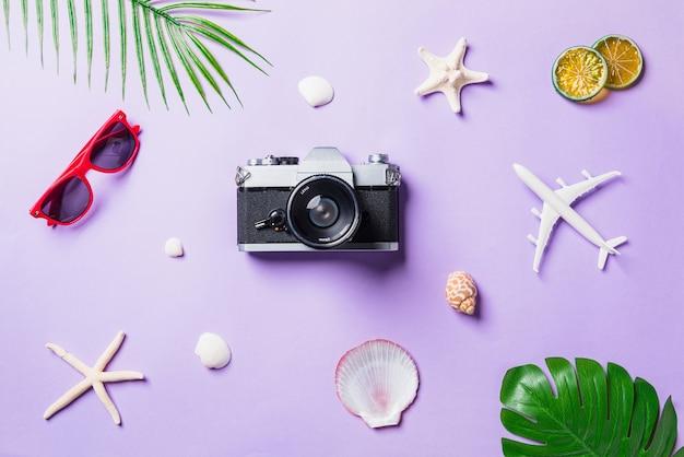Maquete da vista superior de filmes de câmera, avião, óculos de sol, folhas, acessórios para viajantes de praia de estrelas do mar