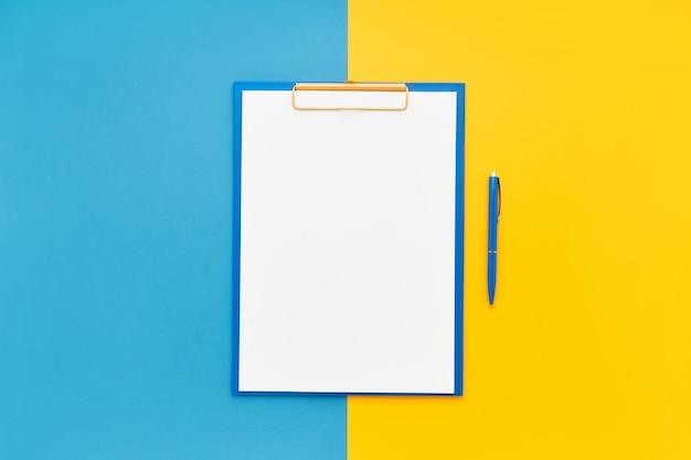 Maquete de área de transferência em branco e caneta esferográfica azul em fundo de cor azul-amarelo