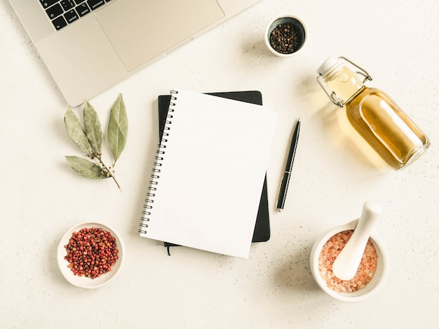 Maquete de bloco de notas de cozinha para texto culinário, laptop, óleo em garrafa e especiarias