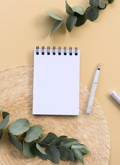 Maquete de bloco de notas mínimo vertical. caderno espiral com espaço de cópia e folhas de eucalipto.