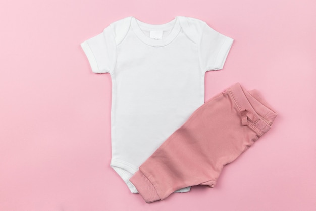Maquete de body de bebê branco com calcinha na superfície rosa
