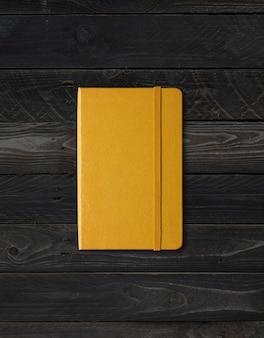Maquete de caderno amarelo fechado isolado em fundo preto de madeira