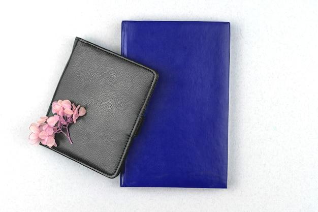 Maquete de caderno de couro, bloco de notas preto e azul com composição de flores secas em fundo de mesa de mesa prateada branca, foto plana e vista superior