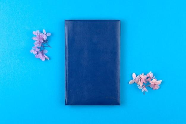Maquete de caderno de couro vazio com flores secas em um fundo azul, foto plana e vista superior