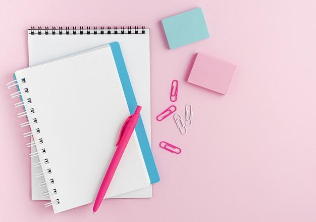 Maquete de caderno em branco branco, caneta e material de escritório em fundo rosa. vista superior, copie o espaço