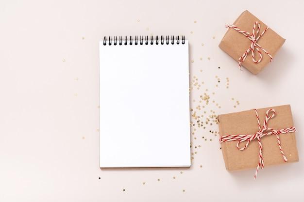 Maquete de caderno em branco, confetes de estrelas douradas, caixas de presente em fundo bege