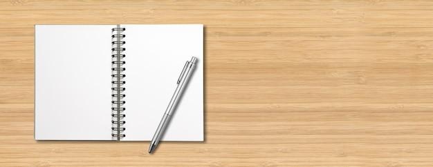 Maquete de caderno espiral aberto em branco e caneta isolada em madeira
