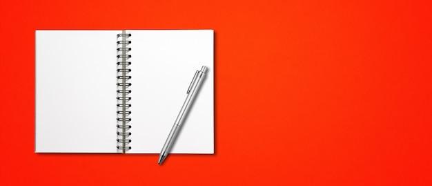 Maquete de caderno espiral aberto em branco e caneta isoladas em banner horizontal vermelho